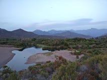 Ciel bleu au-dessus de la rivière avec de beaux arbres méditerranéens Images stock