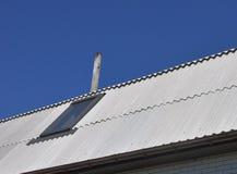 Ciel bleu au-dessus des nouvelles tuiles de toit d'amiante dangereux avec la fenêtre de toit, lucarnes Images libres de droits