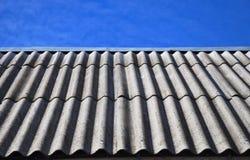 Ciel bleu au-dessus des vieilles tuiles de toit d'amiante dangereux Photos libres de droits