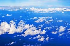 Ciel bleu avec des cumulus d'une fenêtre d'avion images stock