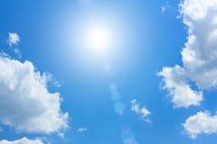 Ciel bleu avec des cumulus et Sun photographie stock libre de droits