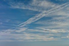 Ciel bleu avec des nuages et des traînées d'avion Belle composition en nature de fond Photo libre de droits