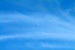 Ciel bleu avec la lune et les nuages Wispy Photos stock