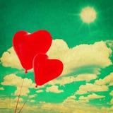 Ciel bleu avec les nuages blancs et les ballons en forme de coeur rouges Photographie stock libre de droits