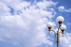 Ciel bleu avec les nuages et la lampe de parc Photographie stock libre de droits
