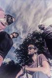 Ciel bleu d'adolescents de groupe avec des nuages photos stock