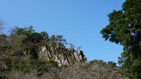 Ciel bleu d'arbre et de pierre et nuages blancs Image stock
