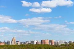 Ciel bleu de ressort au-dessus de ville et de bois verts Image stock