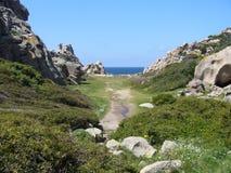 Ciel bleu et mer étonnante, roches de granit avec la végétation méditerranéenne, vallée de lune, della Luna, Testa de capo, Santa Photos libres de droits
