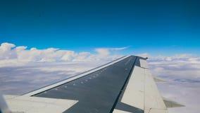Ciel bleu et nuages blancs de tas regardant par le hublot de l'avion 4k de vol banque de vidéos