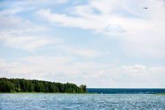 Ciel bleu et nuages blancs, forêt verte et eaux bleues de rivière Photo libre de droits