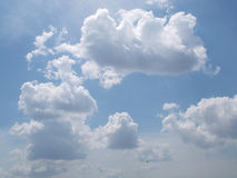 Ciel bleu et nuages gonflés avec le soleil lumineux Photographie stock libre de droits