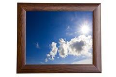 Ciel bleu et soleil dans le cadre de tableau en bois Photographie stock libre de droits