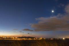 Ciel bleu-foncé de matin avec des nuages la lune et les planètes Images stock