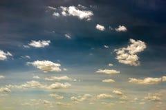 Ciel bleu-foncé vibrant avec le blanc pour jaunir des nuages Beau fond déprimé de nature photo libre de droits