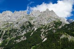 Ciel bleu lumineux de crêtes de montagnes de haute de chaîne de montagne avec des nuages Image libre de droits