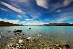 Ciel bleu, montagnes, lac Tekapo dans l'heure d'été Photos stock