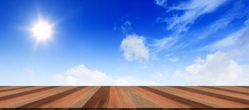Ciel bleu nuageux avec le faisceau du soleil et le plancher en bois Images libres de droits