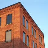 Ciel bleu rouge de coin d'immeuble de bureaux de brique au soleil photographie stock