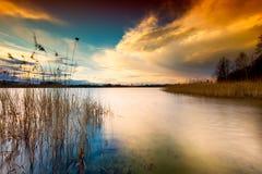 Ciel coloré de coucher du soleil au-dessus de lac dans le long paysage d'exposition Photos libres de droits