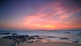 Ciel cramoisi au-dessus de plage rocheuse Photos libres de droits