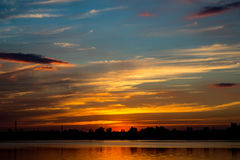 Ciel d'or étonnant de coucher du soleil avec la réflexion sur le lac calme Images libres de droits