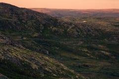 Ciel d'or de lever de soleil au-dessus d'une vallée verte de montagne Photo stock