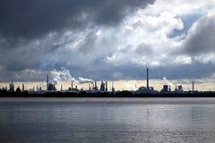 Ciel d'installation de transformation de raffinerie de pétrole et de nuages de tempête Images stock