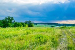 Ciel d'orage sous un pré d'été photos stock