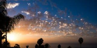 Ciel de coucher du soleil au-dessus de l'eau, des nuages et des silhouettes de palmier Image libre de droits
