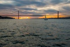 Ciel de coucher du soleil au-dessus du Tage, de pont 25 avril Lisbonne et de port à du bateau, Portugal Photos stock