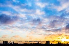Ciel de coucher du soleil avec des nuages au-dessus des maisons urbaines en hiver Images libres de droits