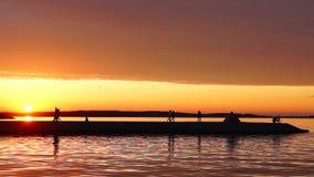 Ciel de coucher du soleil de postluminescence d'été sur le lac de ville banque de vidéos