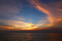 Ciel de coucher du soleil et tache floue de mouvement crépusculaires vifs de la mer dessous avec le long effet d'exposition photo stock