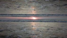Ciel de coucher du soleil de stupéfaction au-dessus de l'océan avec un effet d'horizon de miroir, vue du rivage Vagues sans fin e banque de vidéos