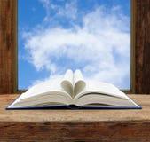 Ciel de fenêtre ouverte de page de forme de coeur de livre Photo stock