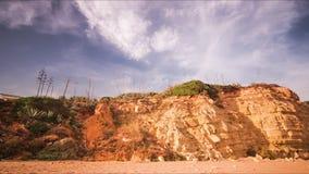 Ciel de laps de temps au-dessus de falaise rocheuse sur la plage sablonneuse Nuages courants en ciel bleu clips vidéos