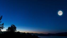 Ciel de minuit avec la pleine lune au-dessus du paysage de rivière Image stock