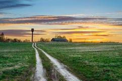 Ciel de soirée à la route de coucher du soleil dans le domaine menant à la tour de grange et d'eau de hangar du paysage rural du  photo stock