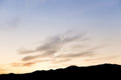 Ciel de soirée et montagne de silhouette de nuages Photographie stock libre de droits