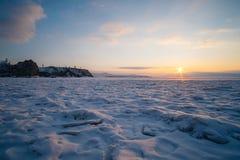 Ciel de soirée pendant le coucher du soleil sur le lac congelé neigeux Image stock
