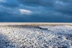 Ciel dramatique au-dessus de paysage gelé de plage d'hiver photo stock
