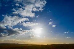 Ciel dramatique avec le yeellow pâle et les couleurs brunes sous des couleurs bleues lumineuses au-dessus d'une forêt vert-foncé  image stock