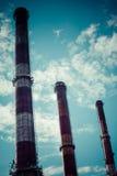 Ciel dramatique et trois cheminées industrielles Photographie stock libre de droits