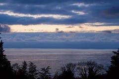 Ciel et mer dans le bleu après le coucher du soleil, encadré par des silhouettes des arbres images stock