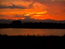 Ciel flamboyant au-dessus de crête et de lac Photos stock