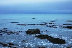 Ciel foncé au-dessus de l'eau bleue laiteuse Image stock