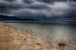 Ciel foncé au-dessus de l'océan, la petite île de GILI Indonesia De l'Océan Indien Images stock
