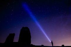 Ciel foncé coloré plein des étoiles avec le grand huit et l'homme de silhouette avec la torche images stock