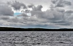 Ciel gris-foncé au-dessus du lac agité photos stock